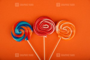 Spiral colored round lollipops on orange background