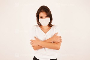 Young woman in medical mask standing
