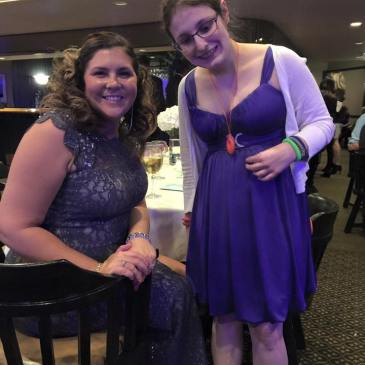 A photo of Chloe Rothschild (on right) with her friend Brittany. Chloe is light-skinned, with glasses, and wearing a purple dress; she has a red fidget necklace around her neck. Brittany is light-skinned, wearing a long lace grey dress, and sitting.