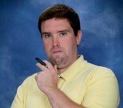 A portrait photo of Brian J Liston holding a pen and wearing a yellow collared shirt.