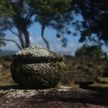 A photo of a lichen covered concrete sphere with a pyramid on top. In the background is a park with trees, a blue sky, and pathway. Photo by Lindsay Ryan.