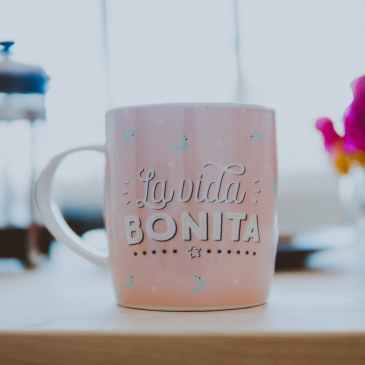 pink and white ceramic mug on brown wooden table