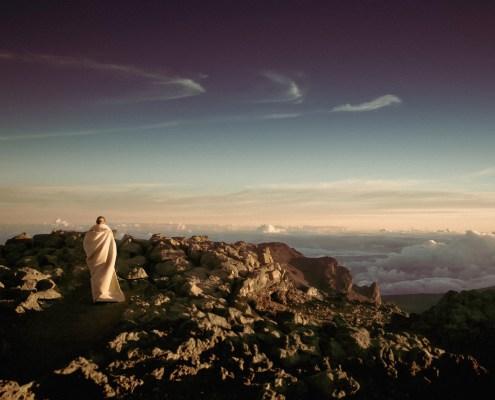 Man in white robe walking in the desert as the sun sets.