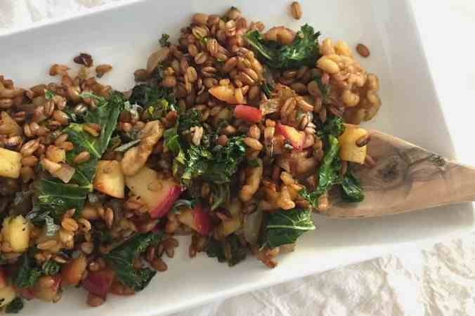 Warm spelt berry salad with kale, apple + walnuts tossed in a cinnamon balsamic vinaigrette. Healthy + vegan thanksgiving dish!