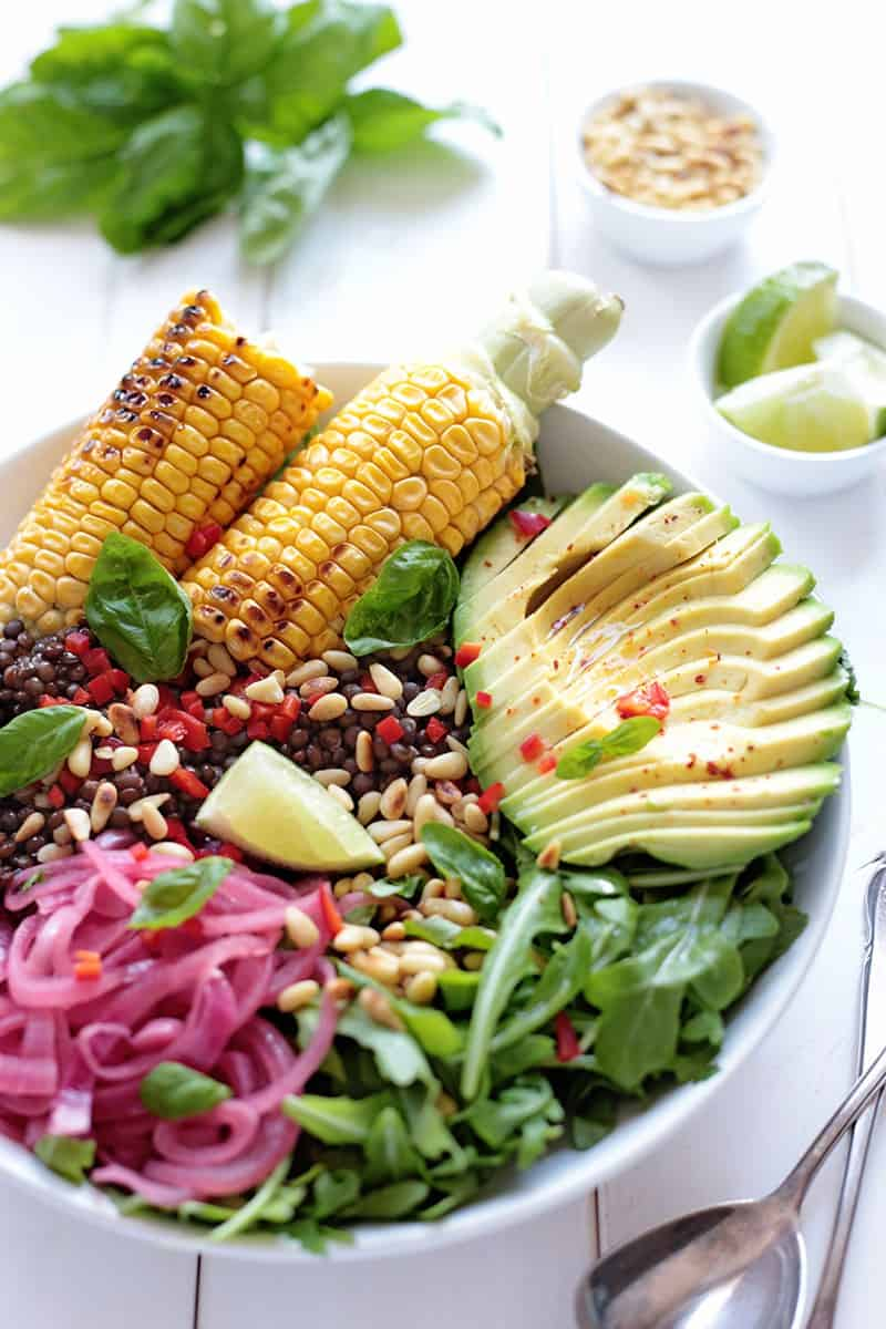 Corn and avocado salad in white bowl against white background.
