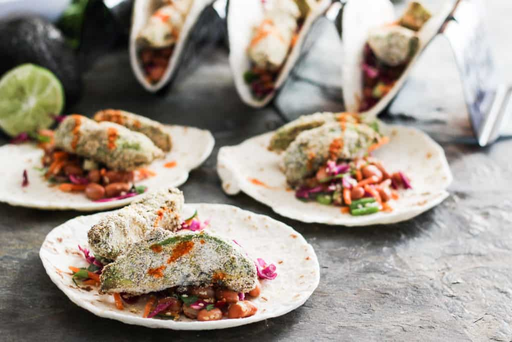 Crunchy avocado tacos make a delicious plant-based lunch or dinner entree that the entire family will love! Served with colorful vegan pinto bean slaw.