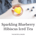 This Sparkling Hibiscus Iced Tea with muddled blueberries, fresh lemon wedges, and spicy grated ginger will make you think twice about plain ice water.