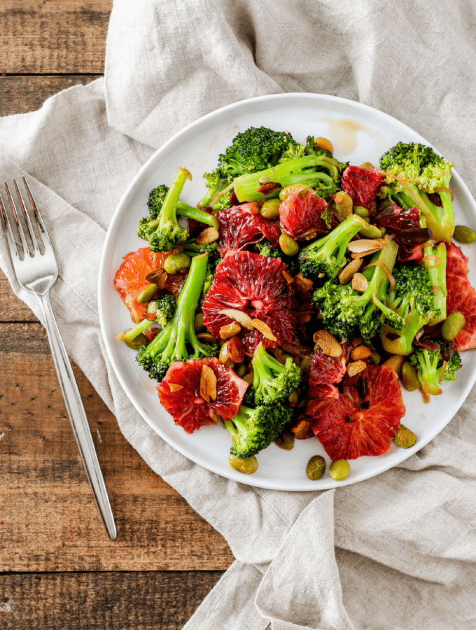 Broccoli Stir-Fry with Blood Oranges on white plate with cream napkin and fork against wood backdrop.