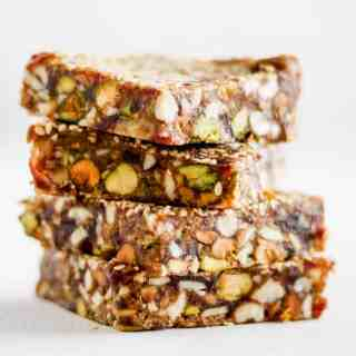 Stack of sesame date bars with pistachios against white backdrop.