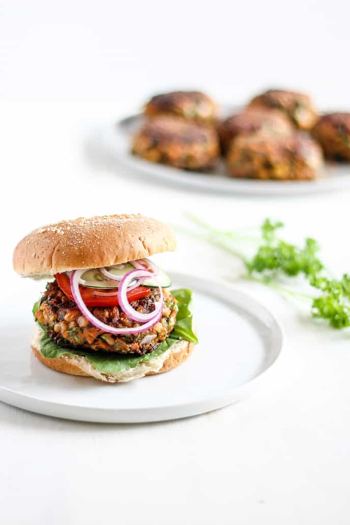 Moroccan Chickpea Burger on a white plate with onion and tomato on a bun. Burger patties in the background.
