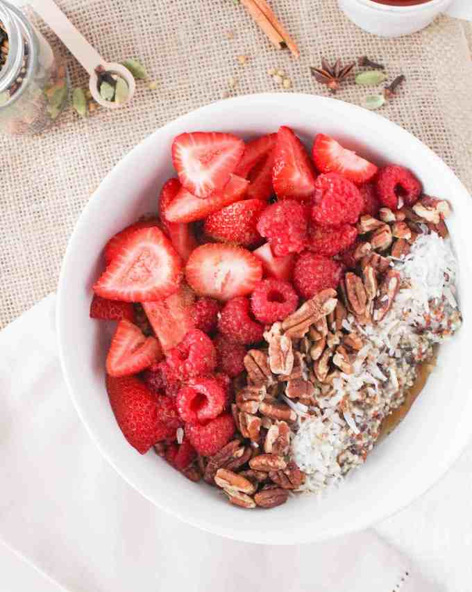 Chai quinoa breakfast bowl topped with strawberries and raspberries. Delicious berry recipes.
