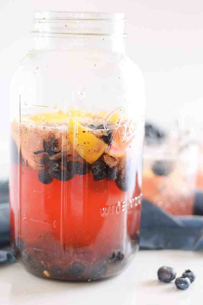 Blueberry hibiscus iced tea in mason jar featured in delicious berry recipes roundup.