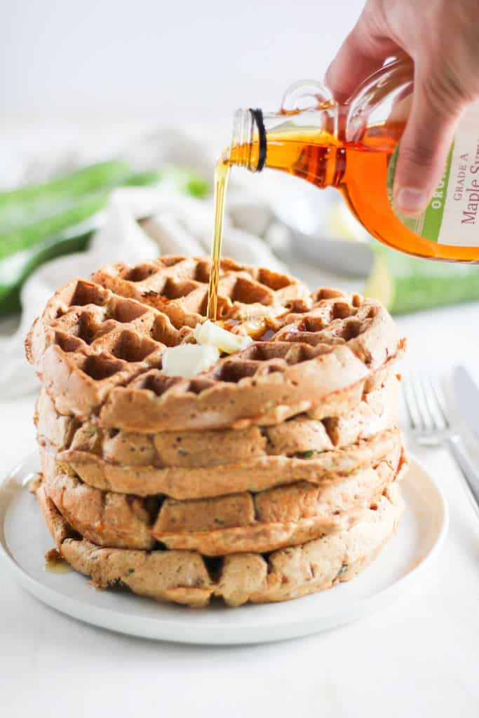 Stack of whole wheat zucchini bread waffles action shot with maple syrup being poured on top.