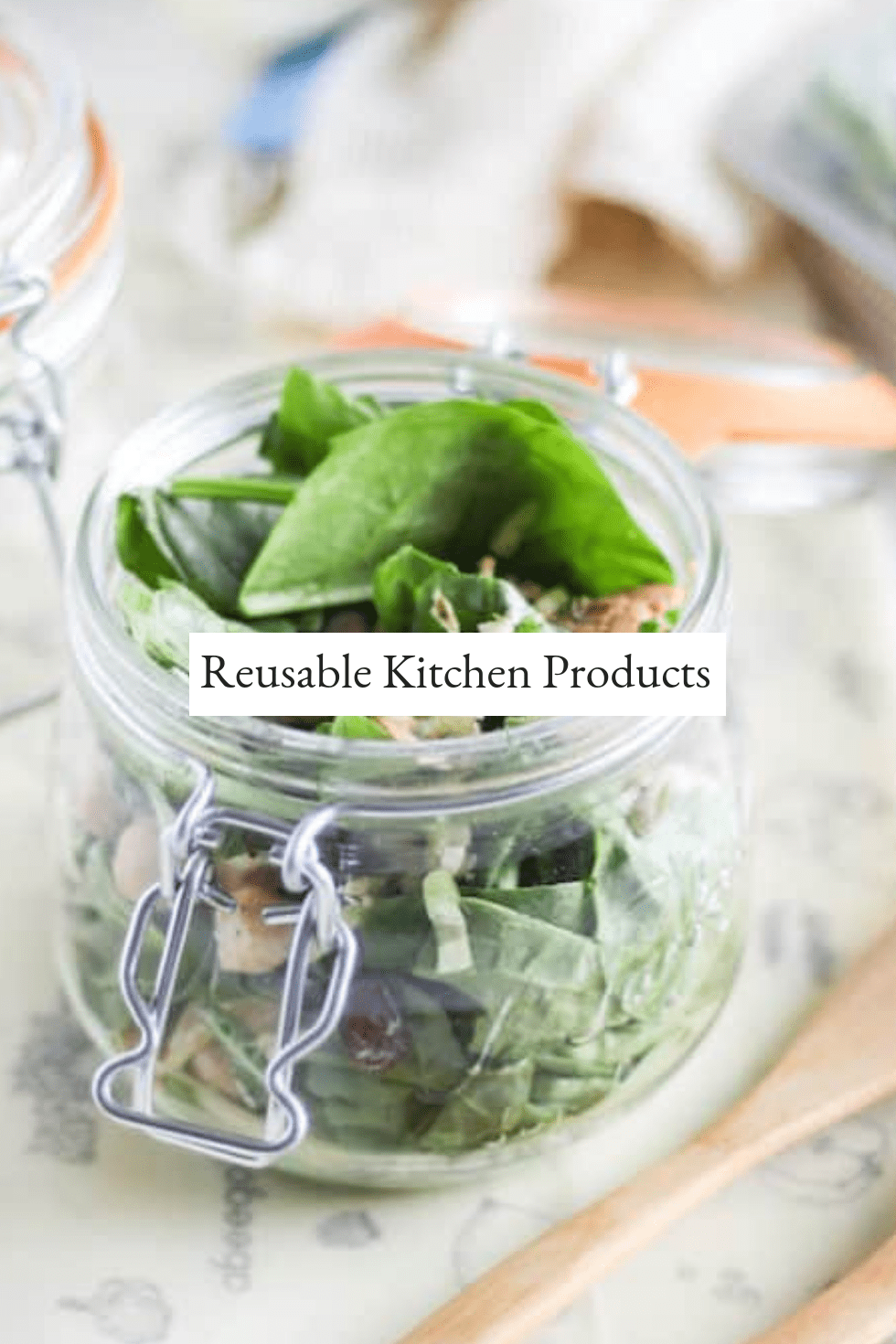 Glass jar filled with salad with bamboo utensils and other reusable kitchen products in background (mesh produce bags, stasher bag, beeswax wraps).