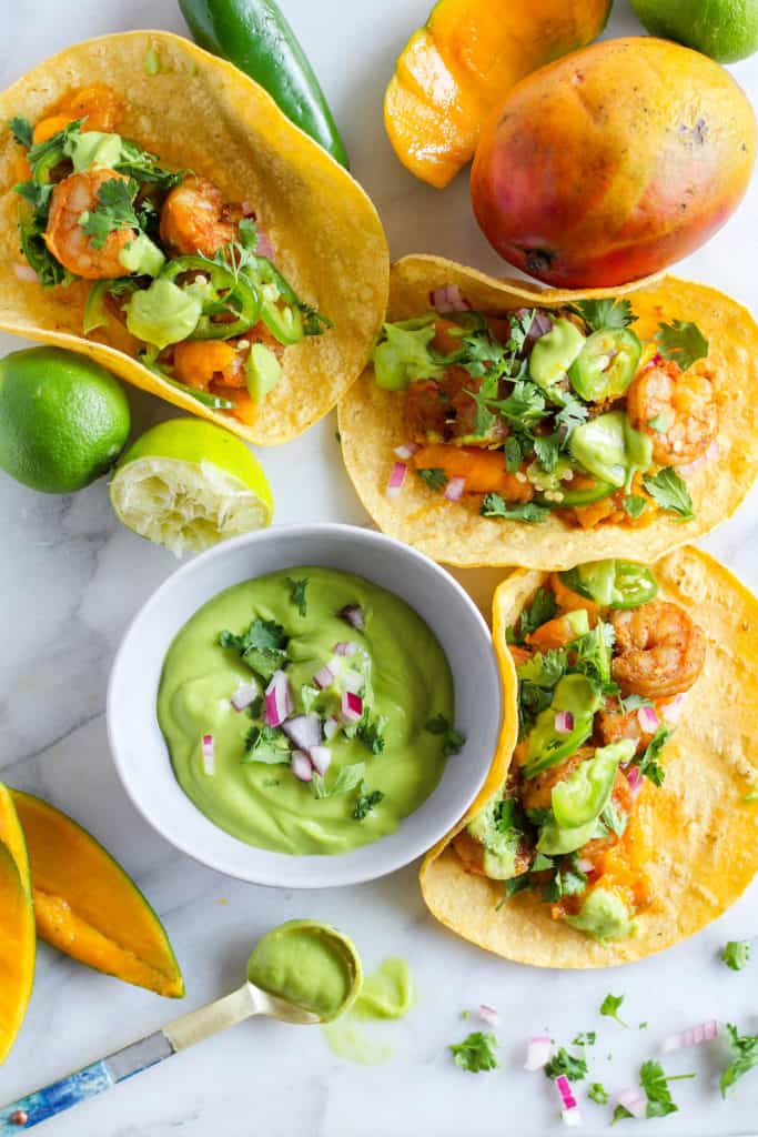 Grilled Mango Shrimp Tacos with bowl of avocado sauce and lime and mango against white backdrop.