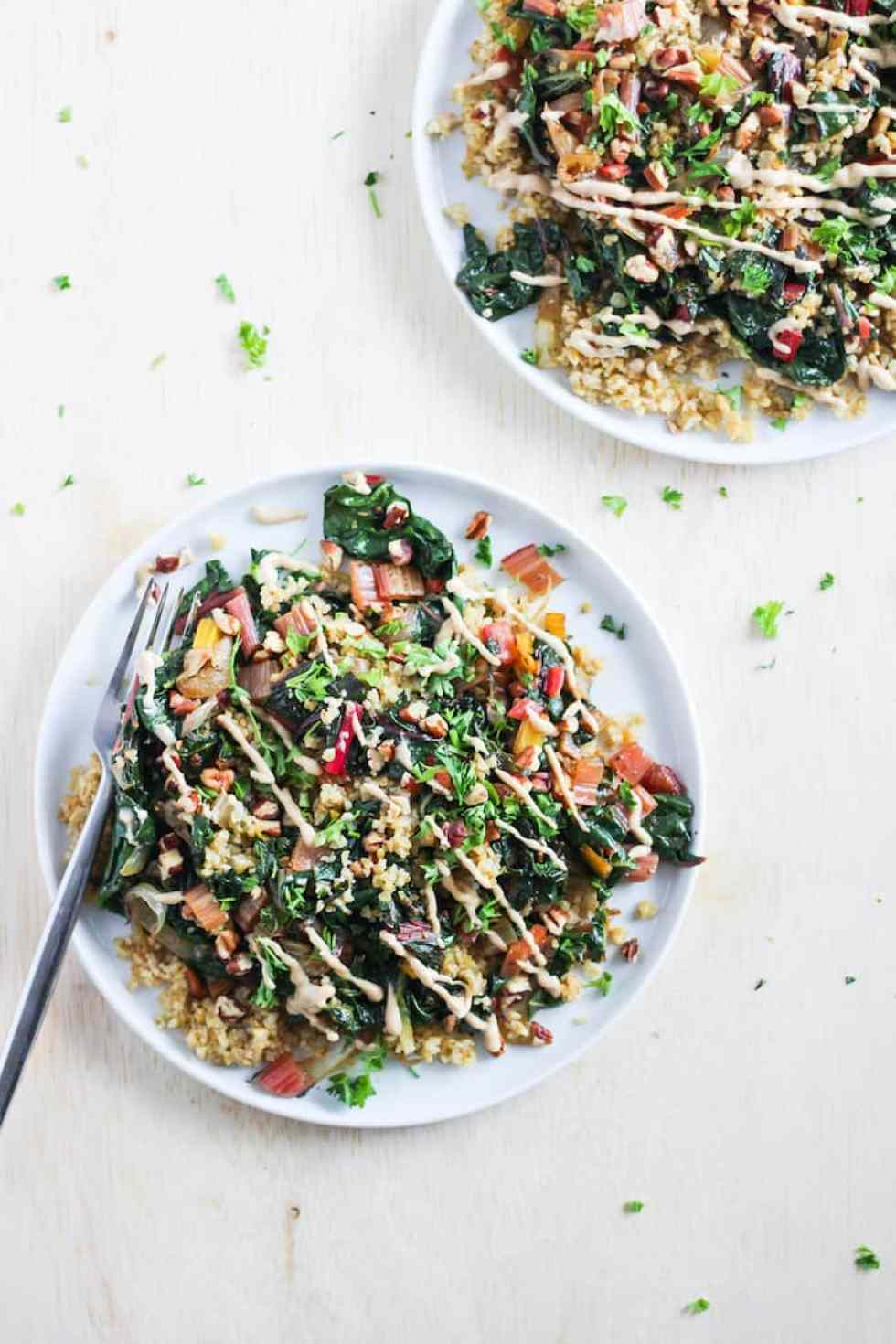 Toasted freekeh and greens on white plates.