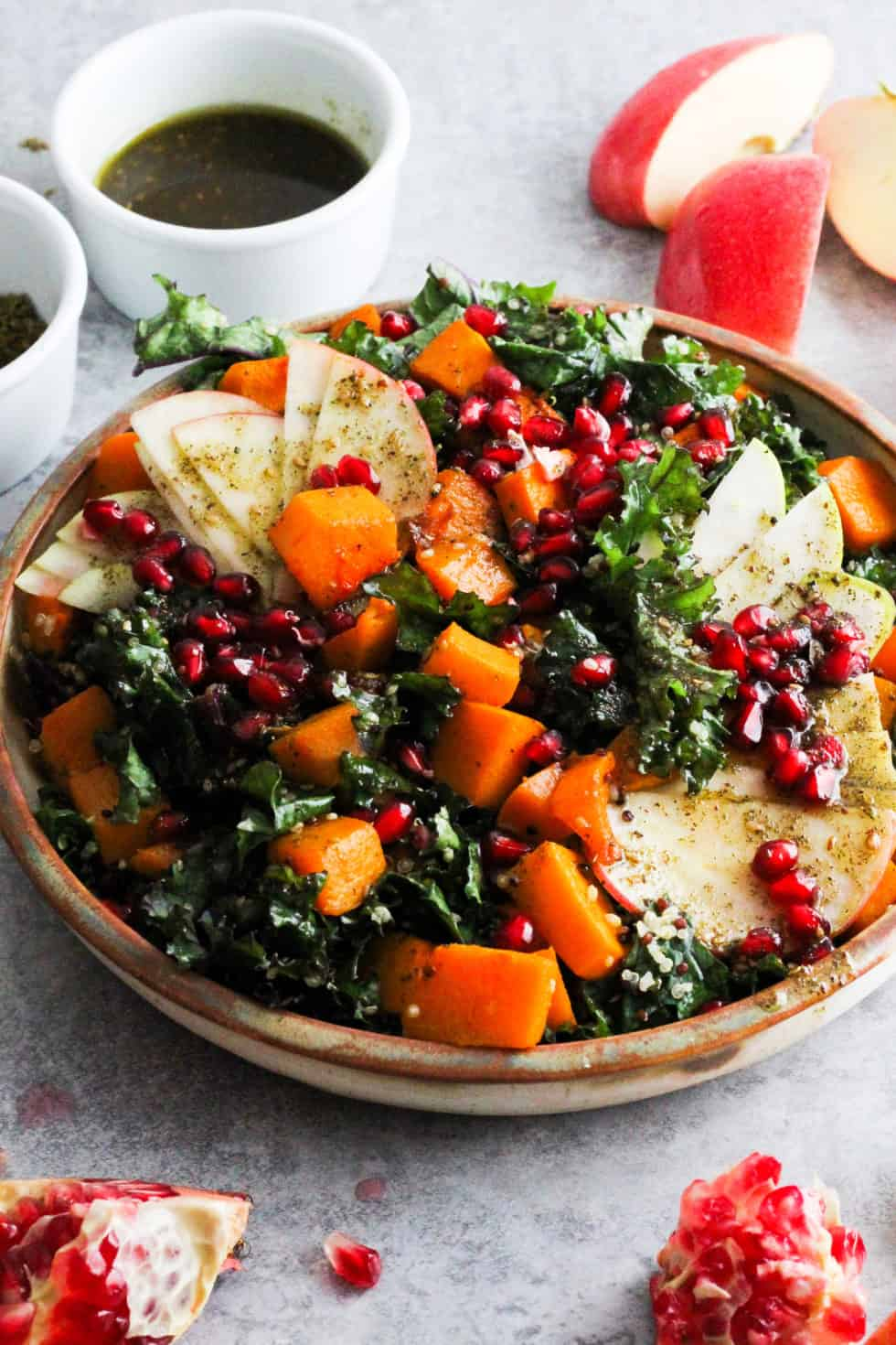 Harvest Zaatar Kale Salad in stone dish with ramekin of dressing and fruit around plate.