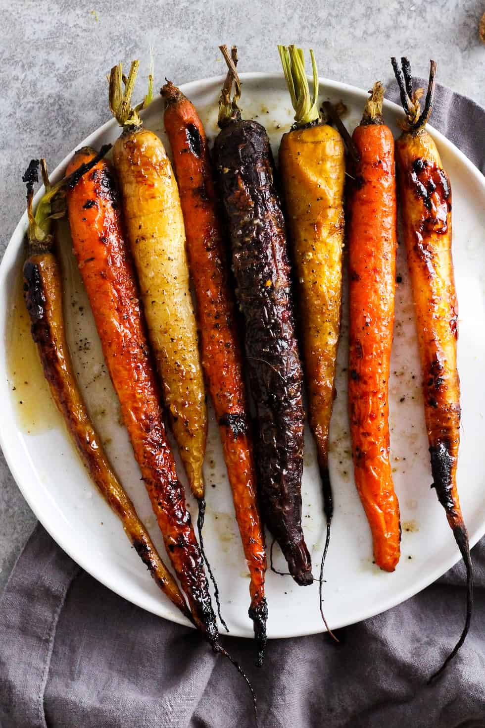 Roasted rainbow carrots on white plate with grey napkin.