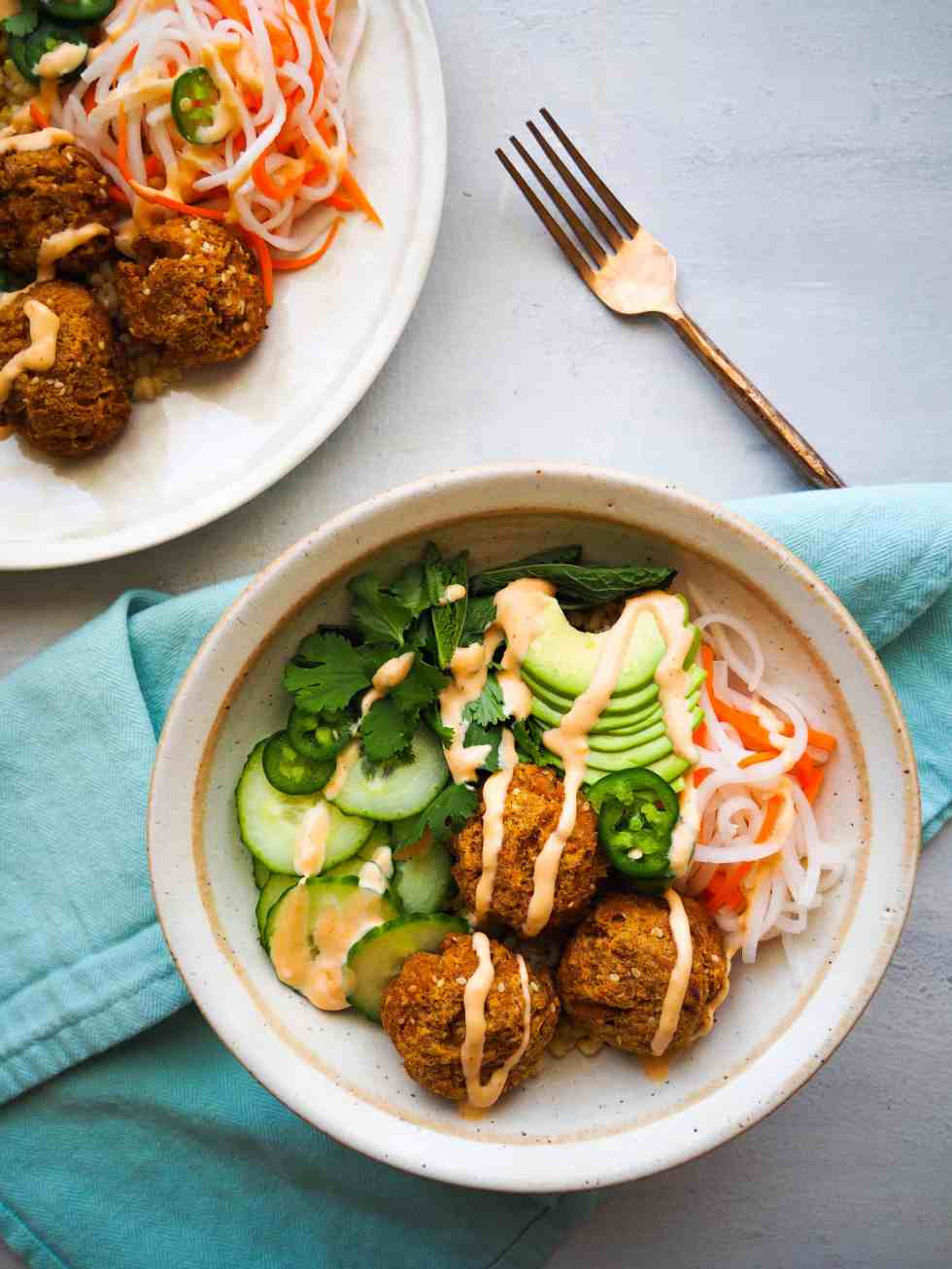 Bowl recipes.Banh Mi Bowl with tofu meatballs in white bowl with blue napkin against grey background.