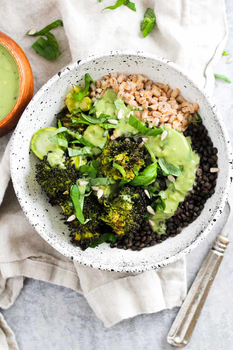 Lentil grain bowls with matcha dressing in white ceramic bowl with cream napkin.