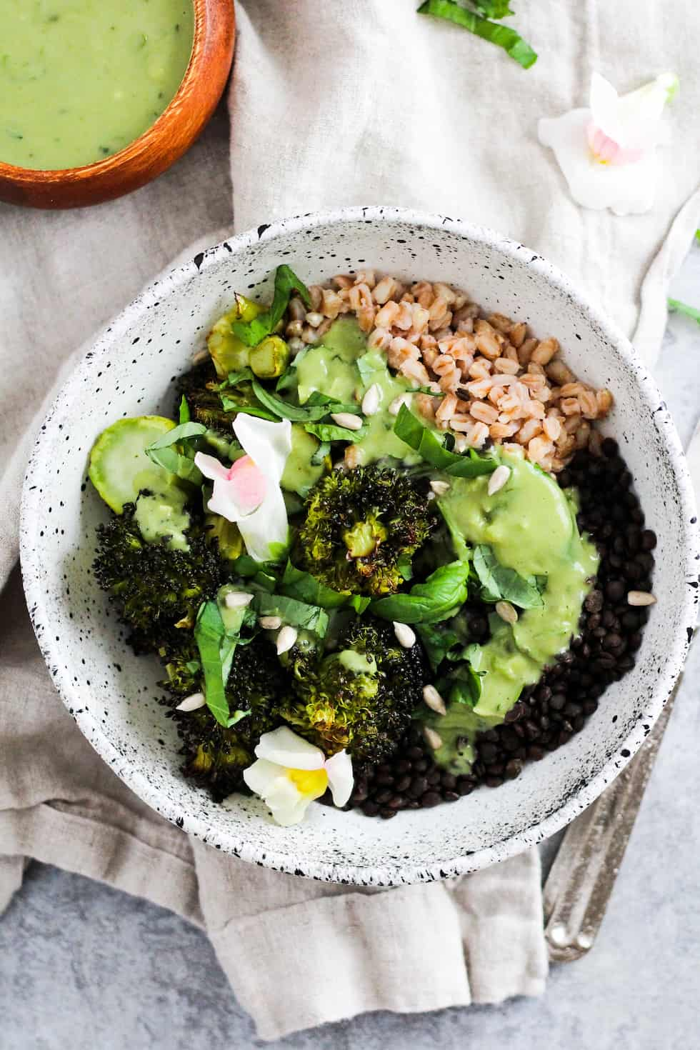 Lentil grain bowls with edible flowers in white ceramic bowl with small wood bowl of green matcha dressing.