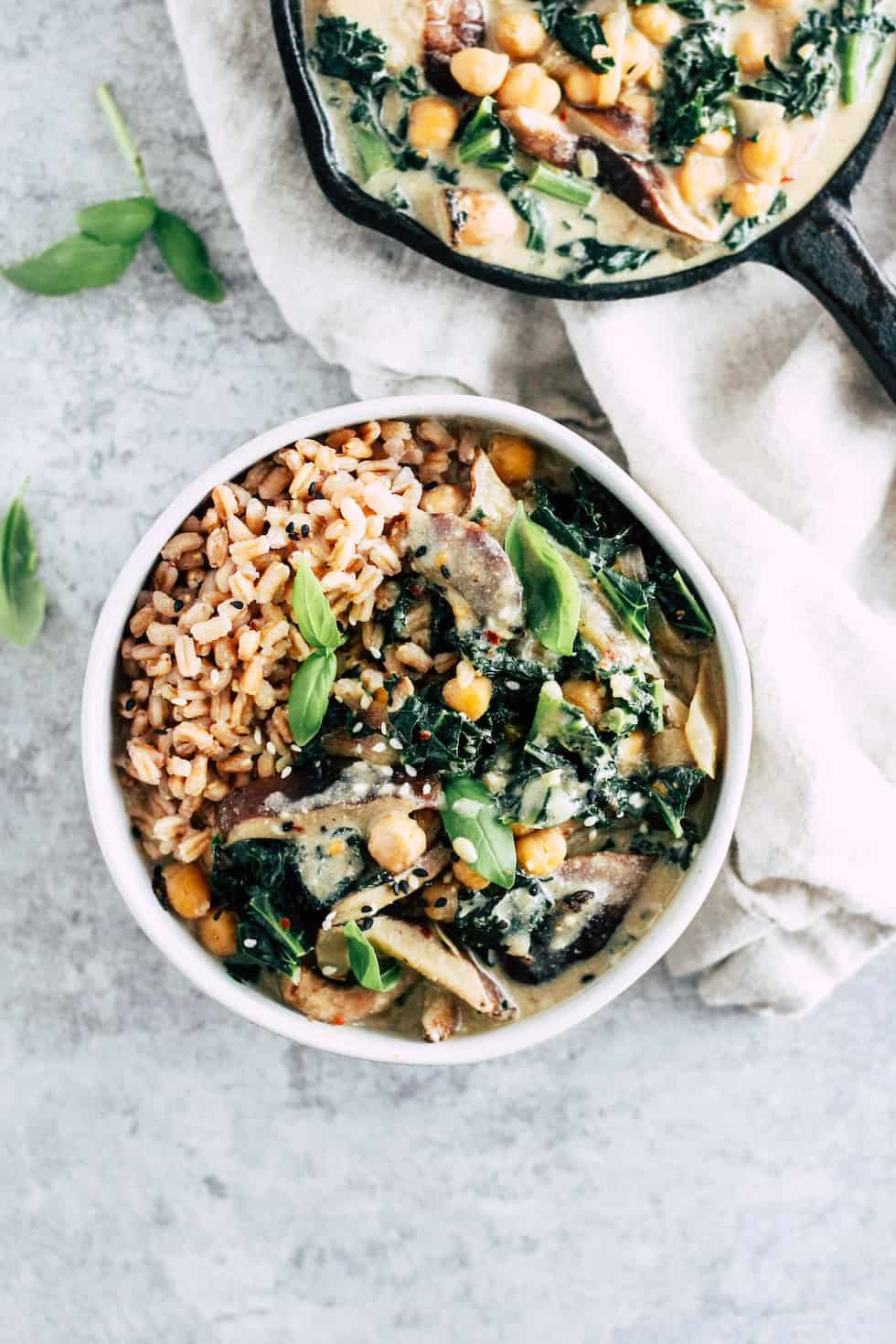 Shiitake mushroom bowls with skillet of creamy miso sauce against grey background with cream napkin.