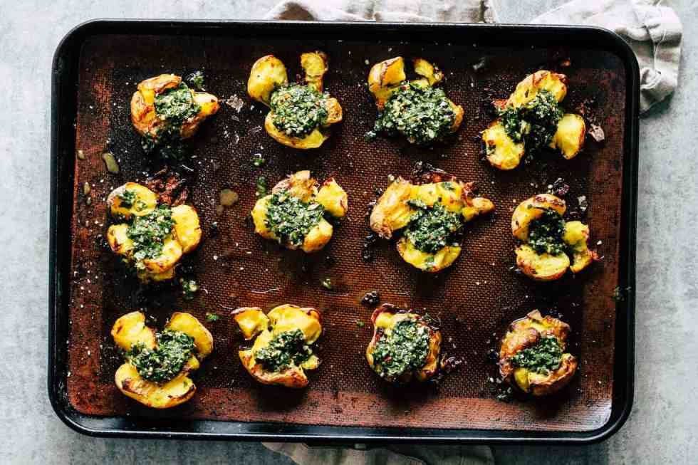 Chimichurri Smashed Potatoes in baking sheet against grey background.