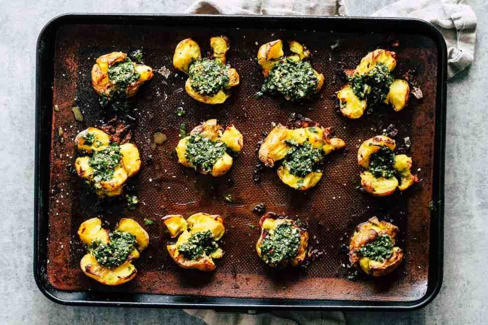 Chimichurri Smashed Potatoes in baking sheet against grey background.