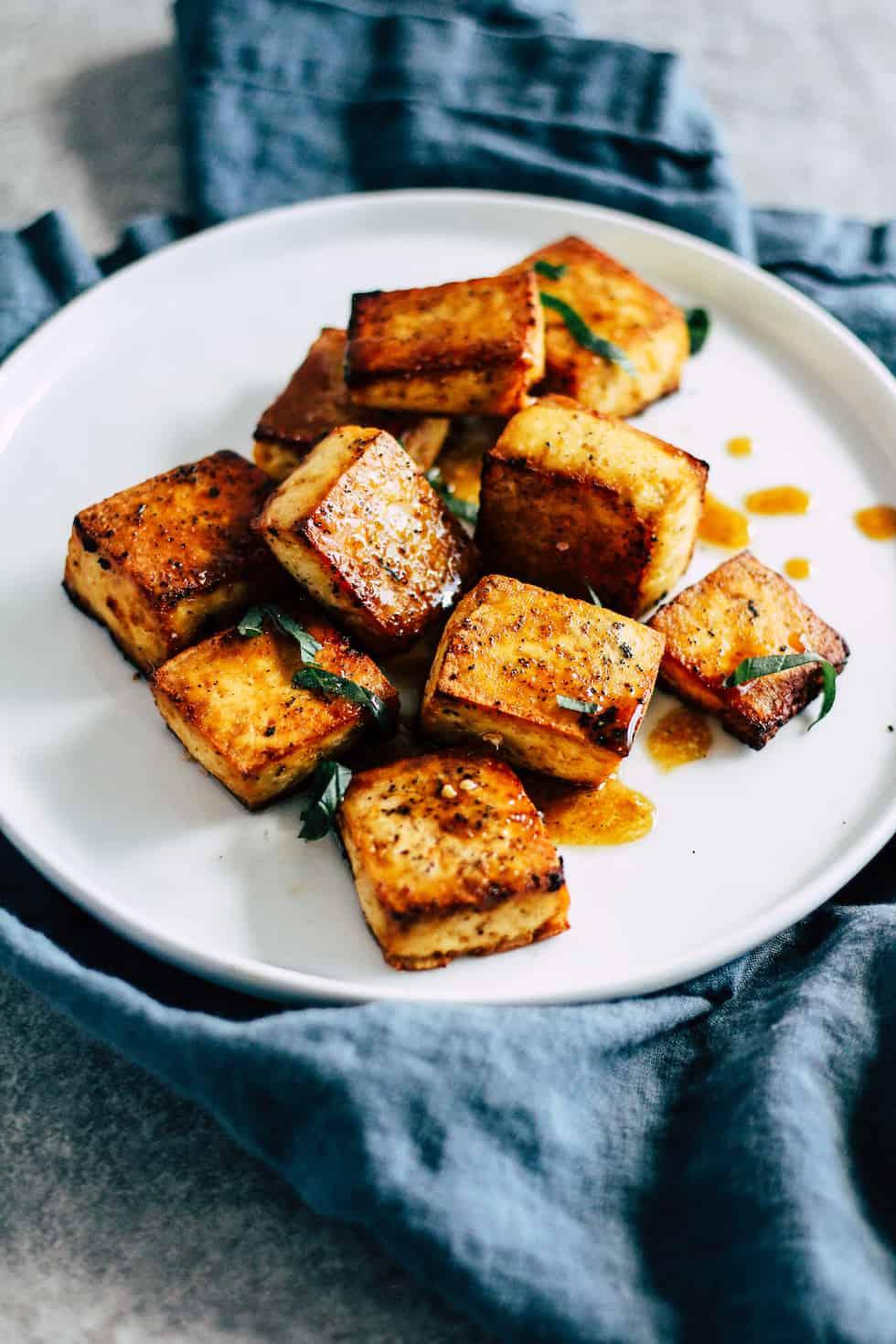 Crispy tofu on white plate with blue linen napkin.