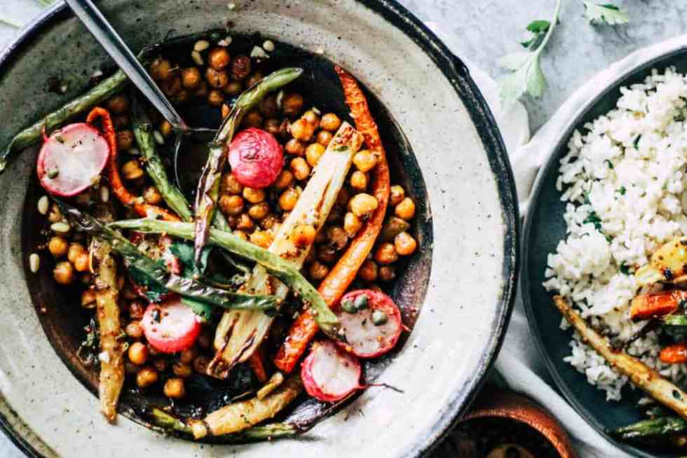Chickpeas, carrots, and radishes in a stone bowl with rice.