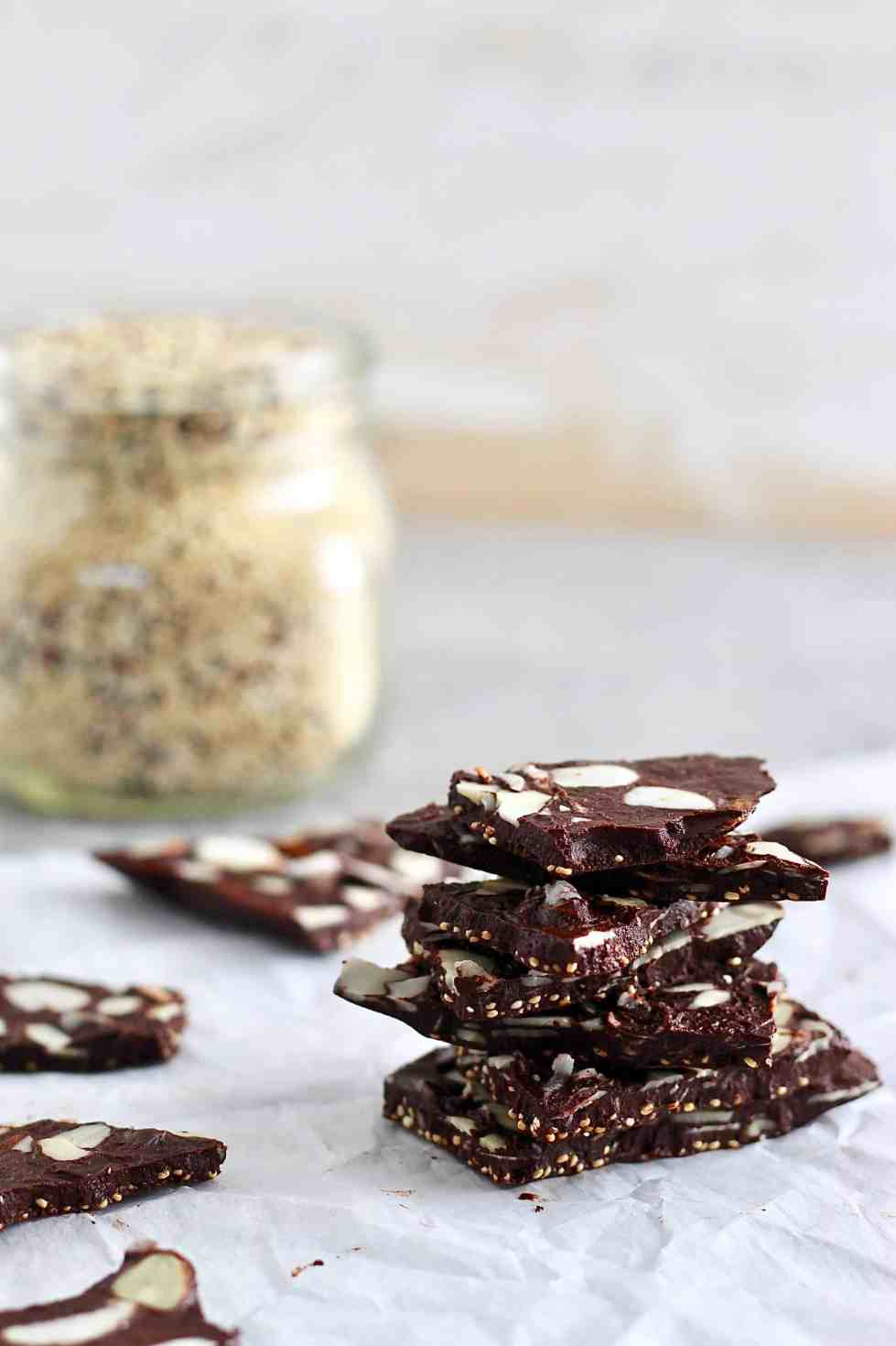 Quinoa crunch chocolate bark with a jar of quinoa in the background.
