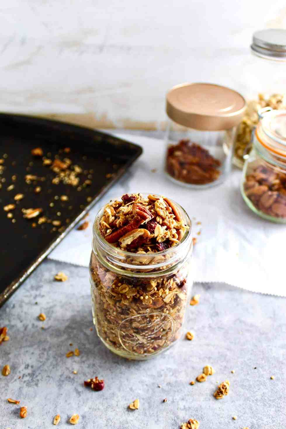 Granola in mason jar with nuts and seeds and a baking sheet in the background.