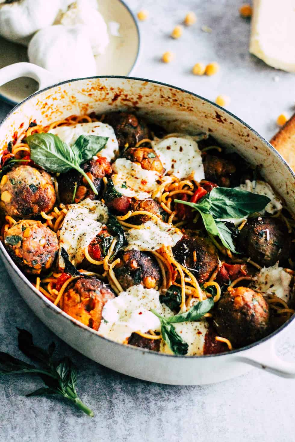 Baked spaghetti and meatballs in white ceramic pot with chickpeas and plate of garlic in the background.