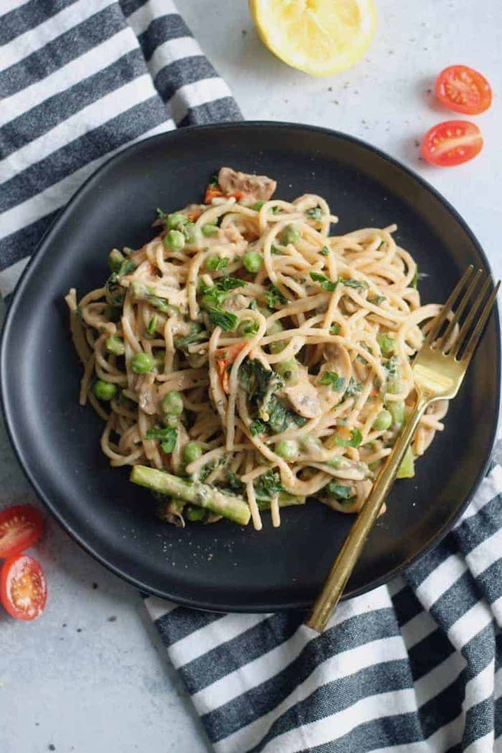 Vegetarian dinner recipes include this creamy spring vegetable pasta on a black plate with gold fork and striped napkin.
