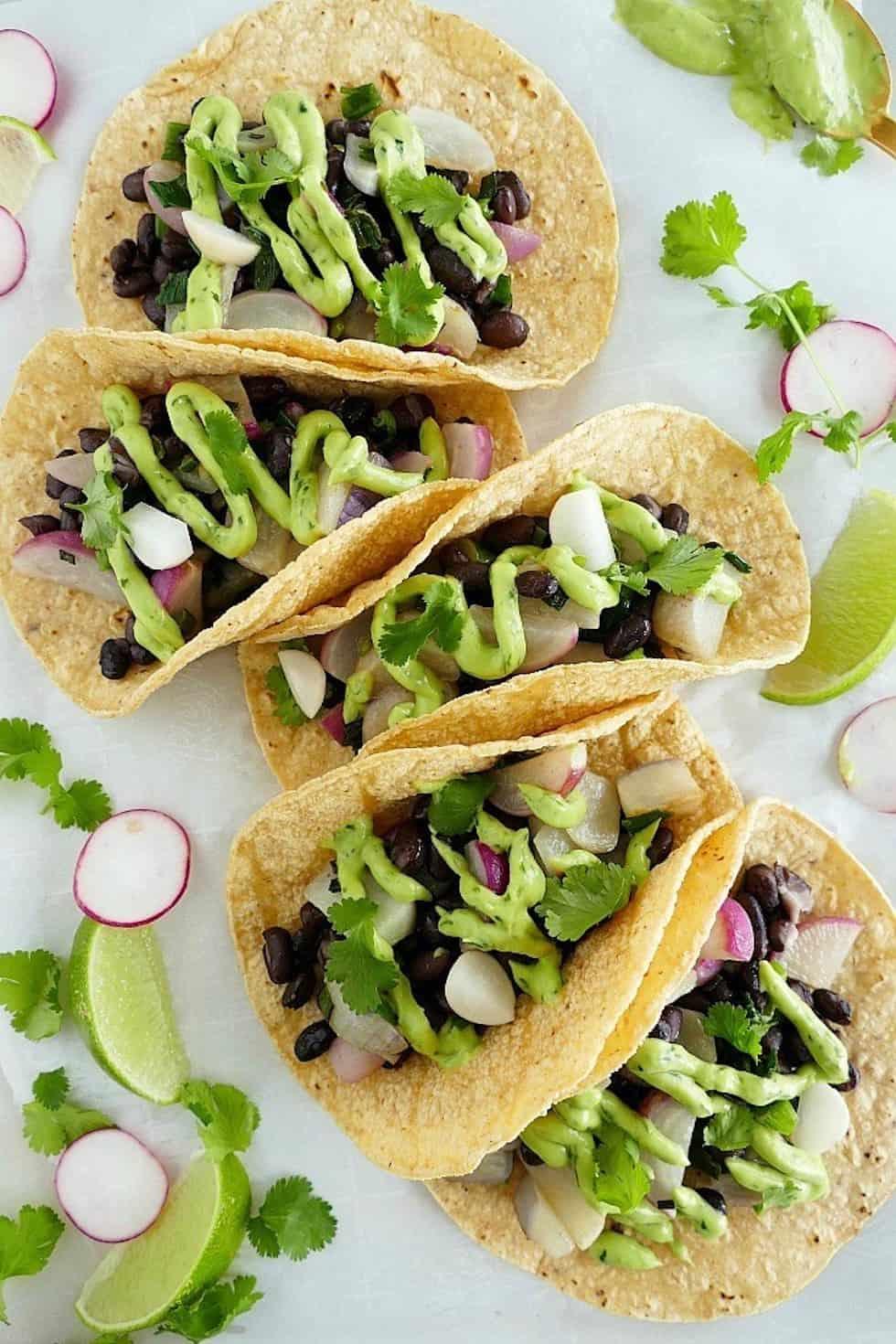 Black bean tacos with avocado crema on white background with limes, radish, and cilantro garnish.