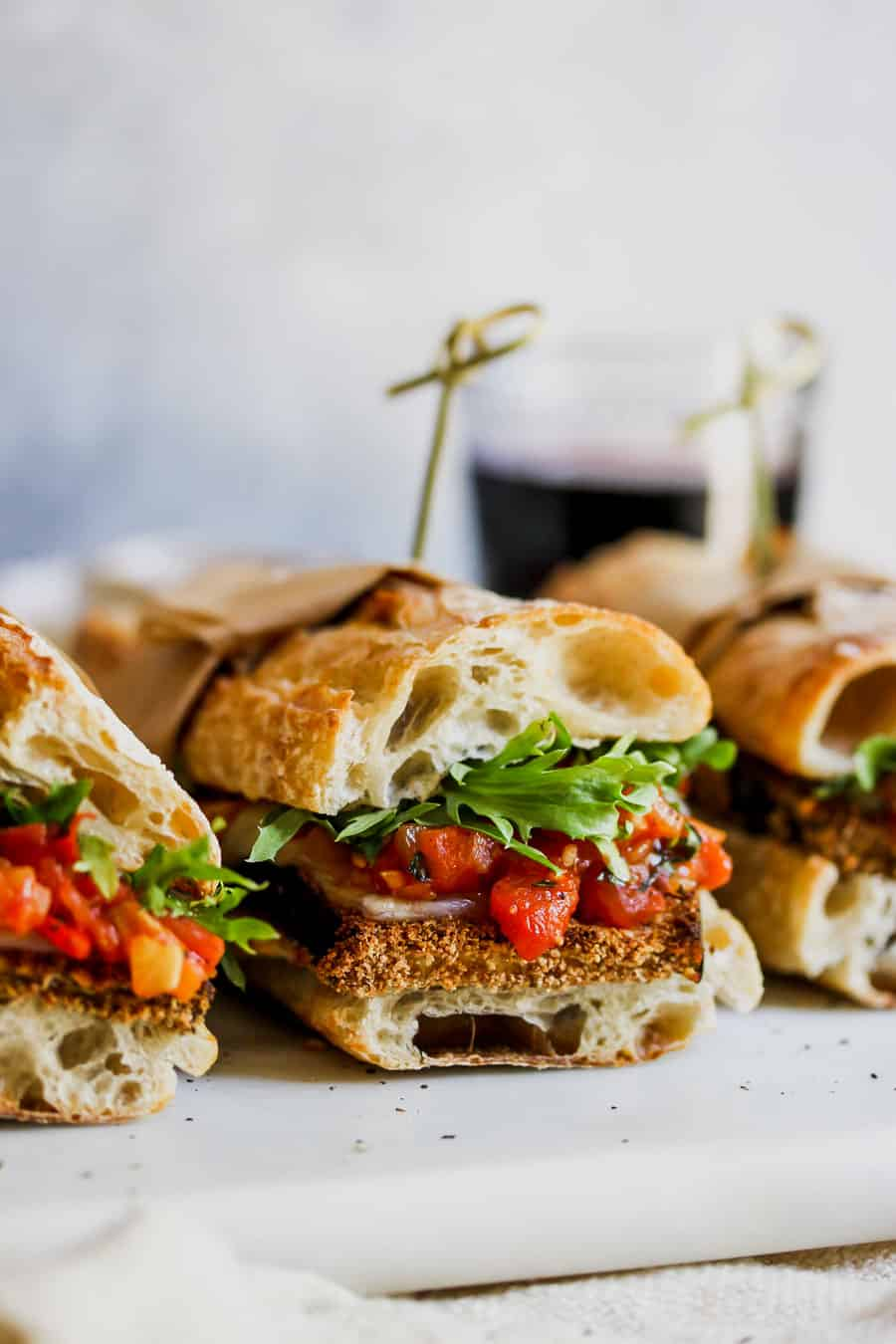 Crispy eggplant sandwiches against white background.