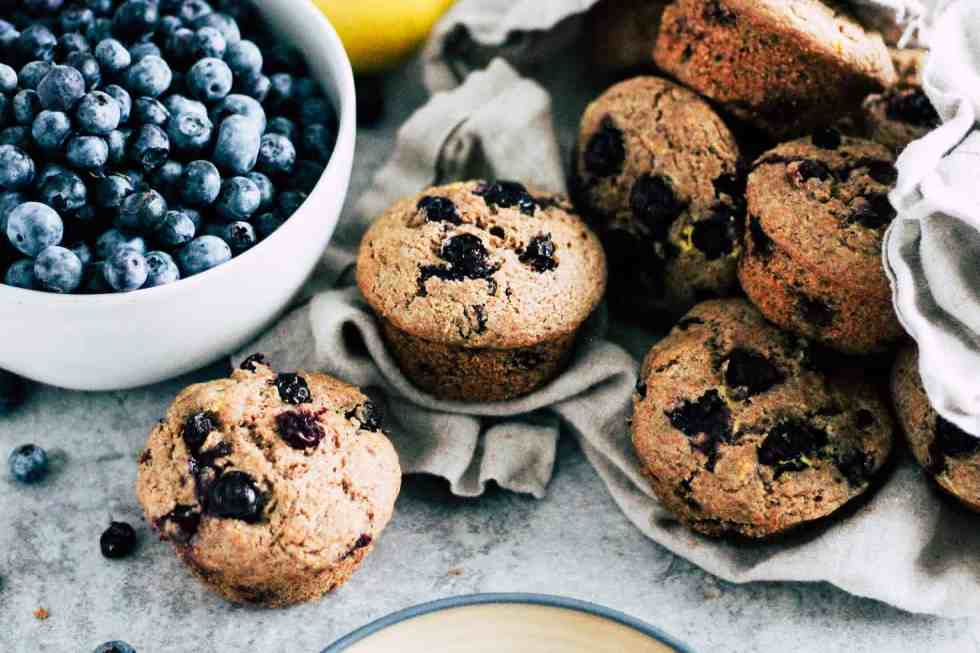 Blueberry muffins in a linen napkin next to a bowl of fresh blueberries.
