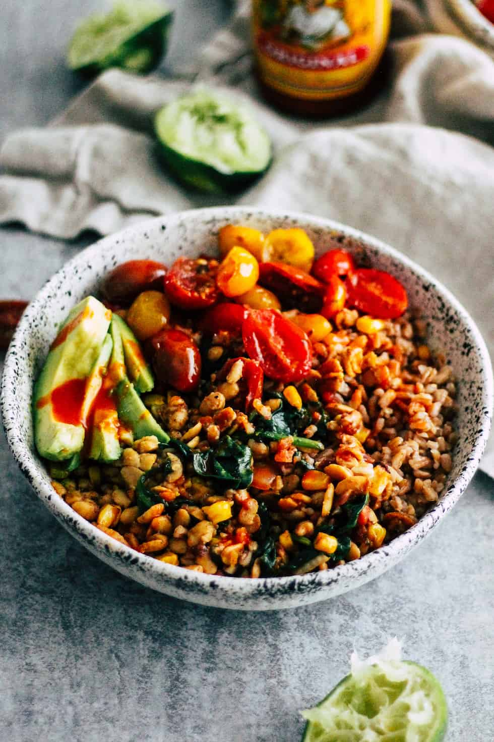 Easy tempeh burrito bowls in white ceramic bowl with lime and hot sauce in the background.