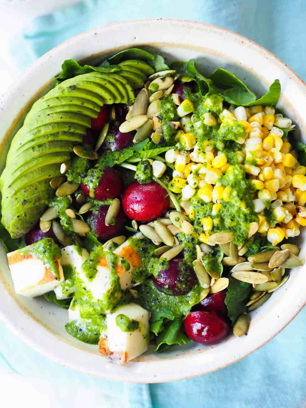 Baby kale salad with avocado and cherries in white bowl with blue napkin.