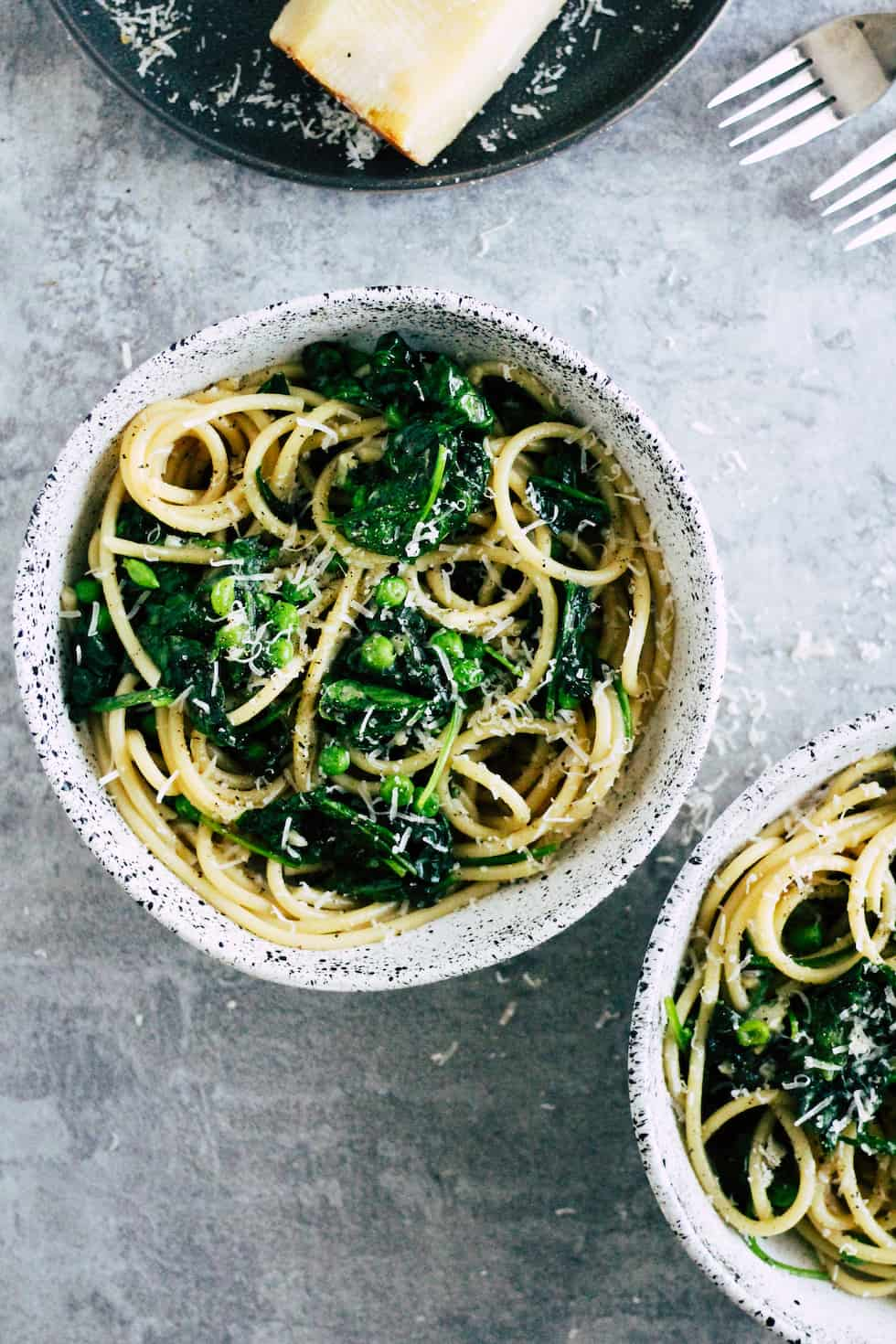 Pasta with spinach and peas in ceramic bowl with wedge of cheese.