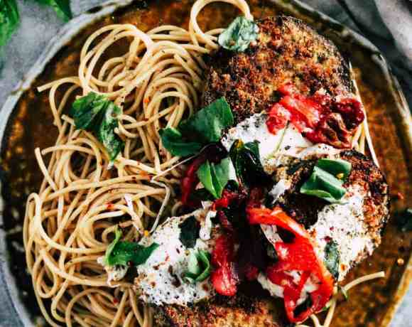 Crispy eggplant with spaghetti on ceramic plate with fresh basil and linen napkin.