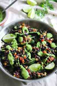 Stuffed poblano peppers in a skillet with green avocado sauce.
