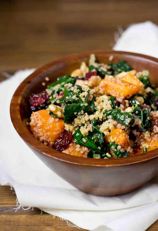 Squash quinoa salad in wood bowl with white napkin.