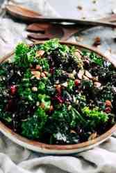 Make-ahead kale salad in ceramic dish with cream napkin.