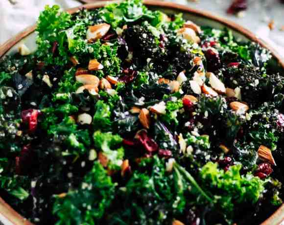 Make-ahead kale salad in ceramic dish with cream napkin.