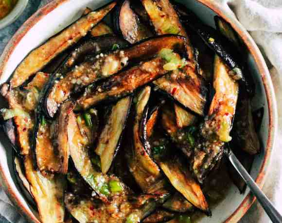 Roasted eggplant in ceramic dish with cream napkin and small bowl of crushed red pepper.