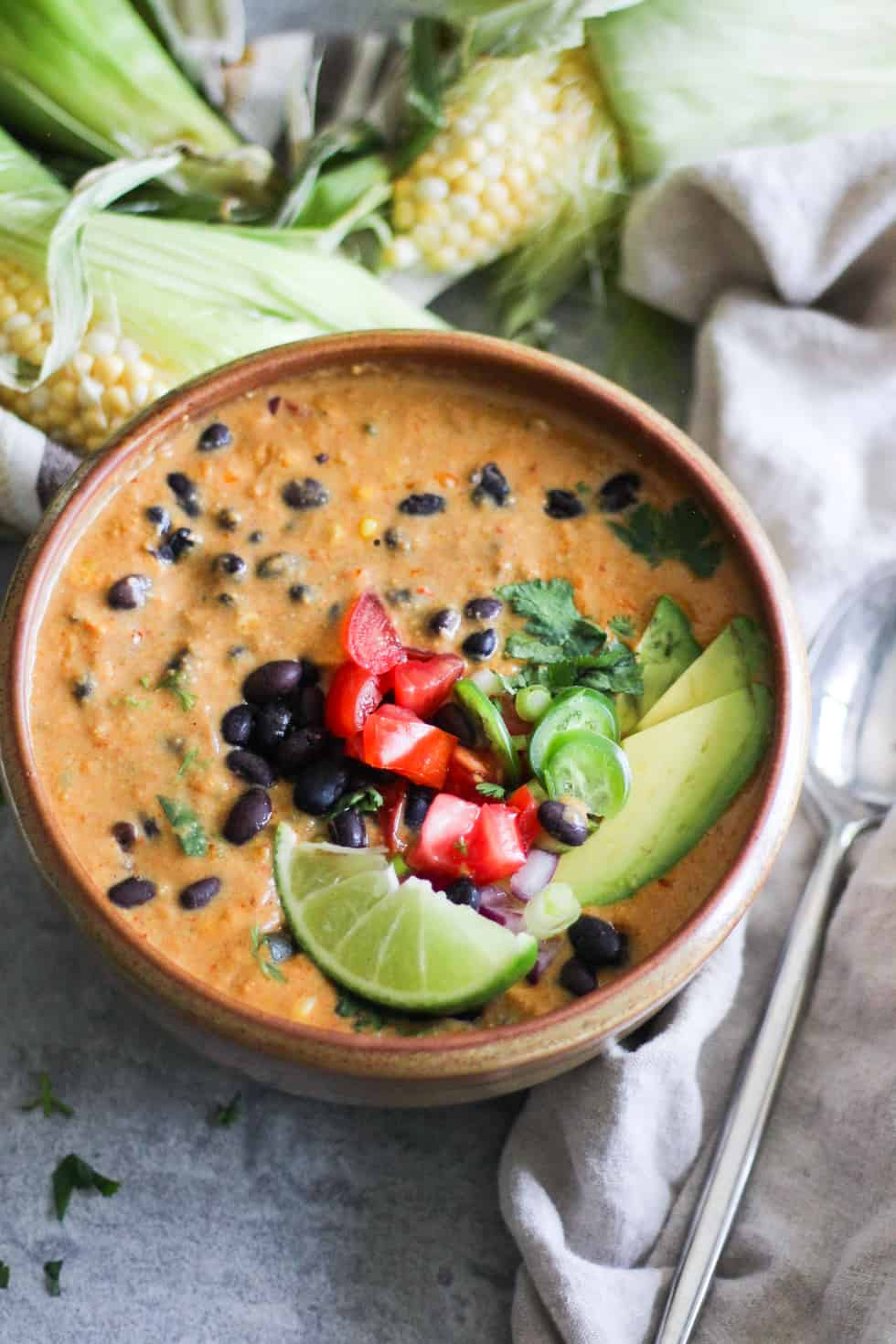 Ceramic bowl filled with soup and topped with avocado, tomato, black beans and lime.