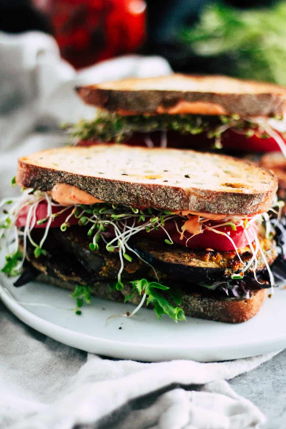 Crispy eggplant BLT sandwich on white plate with lettuce and harissa in the background.
