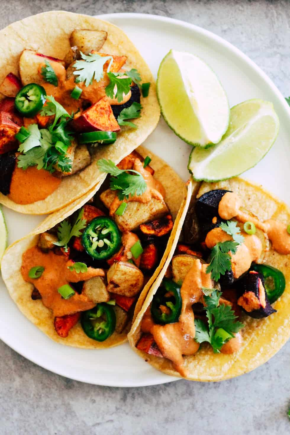 Roasted root vegetable tacos with sunflower seed queso on white plate with lime wedges.