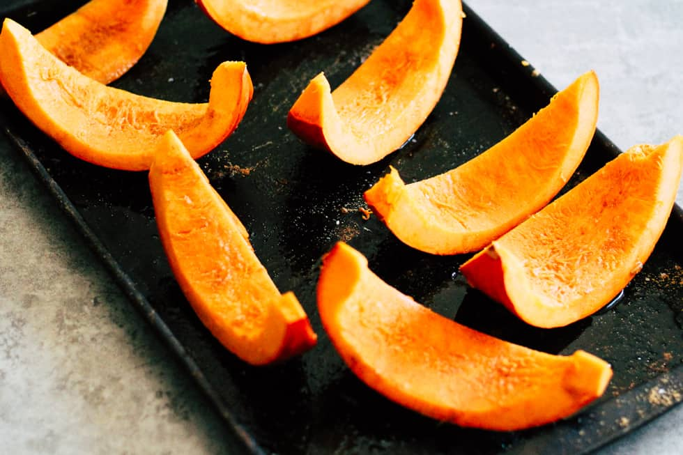 Sliced orange squash on rimmed baking sheet.